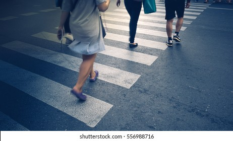 Motion of pedestrian zebra crossing or crosswalk in asia. Feet of the pedestrians crossing on city street closeup.