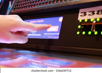 Motion of people pressing redeem button on slot machine inside Casino