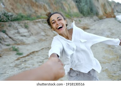 Motion portrait laughing woman holding hand boyfriend and whirling by wild beach, expressive emotions. Real life authentic people