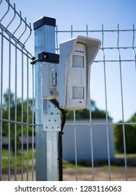 Motion sensor on open protected area. Installed on the fence and connected to the security system with wires. Multifunctional microwave detector. Outdoor guard. Concept of personal or object security.
