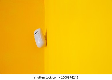 Motion sensor of safety guard alarm on the yellow wall. Concept of security system at home or office.