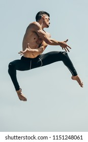 motion shot of attractive shirtless dancer in jump against blue sky
