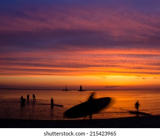 Motion Silhouettes of paddle surfers on a beach against a setting sun.