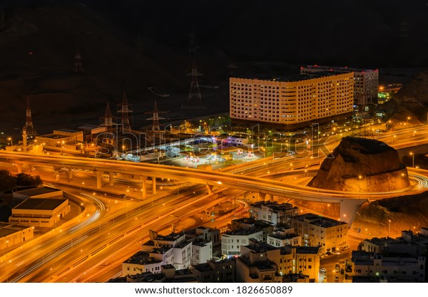 Motion trails and traffic of an illuminated Muscat city in the evening.