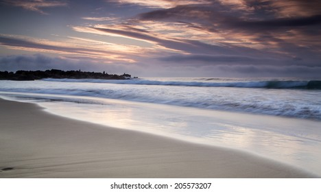 The motion of the waves creating an abstract scene at sunrise on an overcast day