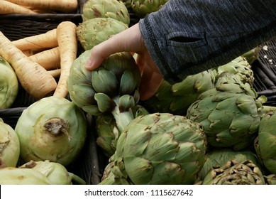 Motion of woman's hand picking artichoke inside Superstore