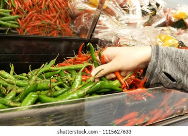 Motion of woman's hand picking green and red hot pepper inside Superstore