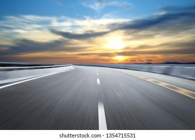 Motion-blurred highway in dusk clouds