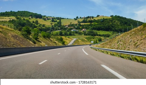 Motion-blurred photo shot from car driving at high speed on the motorway A75, which crosses the beautiful mountain landscape of Auvergne, with country houses on a verdant hillside in the background