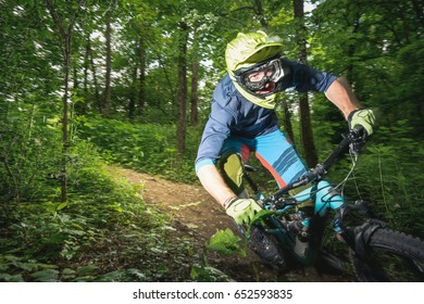 Motion-Blurred shot of a Professional Mountain biker in full face helmet with his enduro bike riding with high speed on a forest trail. Notice the small plant cut on his right hand.