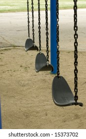 Motionless swings on a sandy playground.