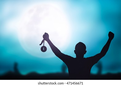 Motivate concept: Winner hand raised and holding gold medal reward against full moon on blue night sky background