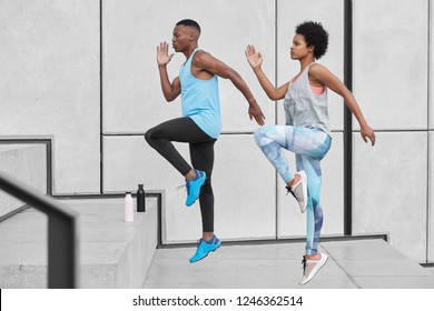 Motivated active ethnic couple run up stairs together, jump highly, train climbing staircase in city, wear comfortable sportsclothes, drink water from bottle, climb challenge, choose difficult path