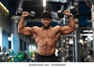 Motivated african american man bodybuilder working on biceps, weight exercises concept. Muscular black guy doing workout with dumbbells at gym, lifting weight up with both hands