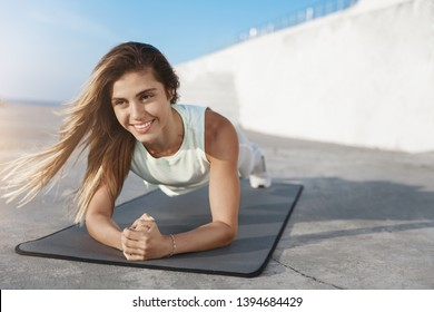 Motivated attractive healthy caucasian sportswoman smiling during plank strenghths exercise, doing front hold easily using fitness mat, enjoying morning workout pier, traning quay facing sunrise