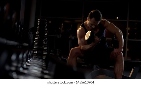 Motivated bodybuilder doing seated isolated dumbbell curl, evening workout