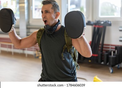 Motivated boot camp instructor stands with focus mitts in gym hall. Training with extended arm on wooden floor. Portrait for fitness concept.