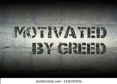 motivated by greed stencil print on the grunge white brick wall
