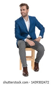 Motivated casual men looking to the side hopeful and smiling while leaning on his leg and wearing an elegant suit, sitting on white studio background