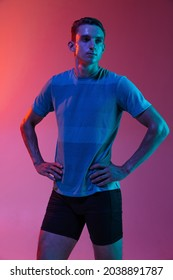 Motivated, composed. Portrat of Caucasian young sportive man in sportswear standing isolated on pink background with blue neon filter, light. Concept of action, motion, speed, healthy lifestyle. - Shutterstock ID 2038891787