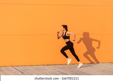 Motivated confident fit woman athlete in tight sportswear, black pants and top, starting to run, jogging outdoor against orange wall, advertising area. Health care and weight loss, sport activity