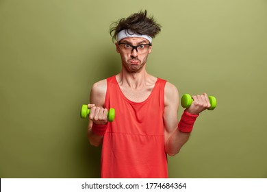Motivated determined sportsman leads sporty lifestyle, lifts heavy dumbbells for muscle training, does morning fitness at home, wants to have biceps, wears red shirt and wristband, looks sadly