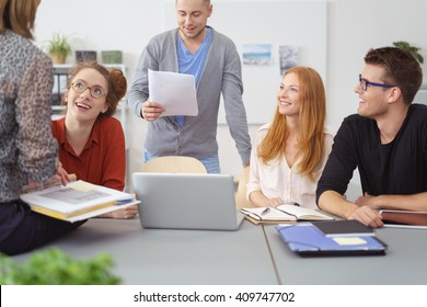 Motivated diverse young business team having a meeting grouped around a laptop computer and engaging in animated discussion of their project
