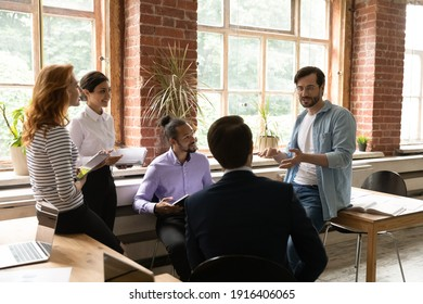 Motivated diverse young multiracial businesspeople talk brainstorm discuss company business project at office meeting. Multiethnic colleagues engaged in team discussion at briefing. Teamwork concept.