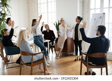 Motivated employees raising hands, asking coach at training. Presenter finishing workshop with questions from engaged audience. Indian female business leader interacting with team at corporate meeting