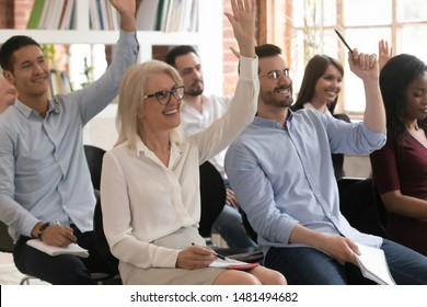 Motivated excited diverse employee raise hand taking part in teambuilding activity at company training, smiling multiracial workers volunteer vote participate in company business seminar in office