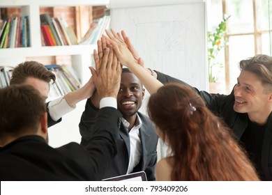 Motivated excited multiracial business team giving high five celebrating corporate growth and financial success, diverse group of colleagues join hands together showing unity help support in teamwork