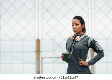 Motivated fitness woman drinking detox green smoothie during outdoor city workout rest. Sport nutrition and healthy lifestyle concept.