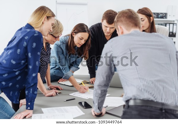 Motivated group of young business people grouped around a table listening to a female team leader or manageress explain paperwork