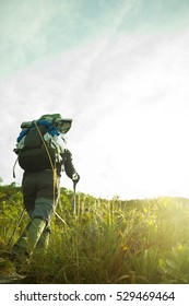 Motivated Hiker walking during the sunset wearing a backpack and trekking poles - Copy Space