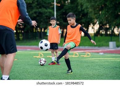 Motivierter Kinderspieler in Fußballuniform, der zusammen mit seinem erfahrenen Trainer auf dem Sportplatz den Kicker ausarbeitet
