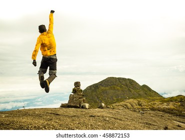 Motivated Man Jumping Celebrating Success with the view of a Mountain (on Serra Fina - Brazil)