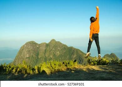 Motivated Man in Orange Jumping Celebrating Success with the view of a Mountain