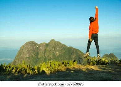 Motivated Man in Red Jumping Celebrating Success with the view of a Mountain