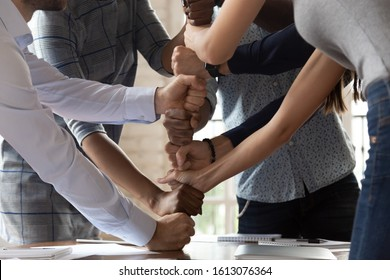 Motivated multiethnic employees involved in teambuilding activity at office meeting, diverse young colleagues stack fists engaged in motivational training show unity, support and team spirit