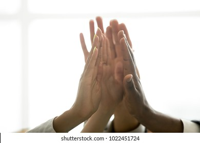 Motivated multiracial business team join hands palms together, black and white diverse people group give high five as concept of successful teamwork and help support unity in common goal achievement