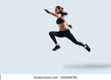 Motivated to shape her body. Full length of attractive young woman in sports clothing exercising while hovering against grey background