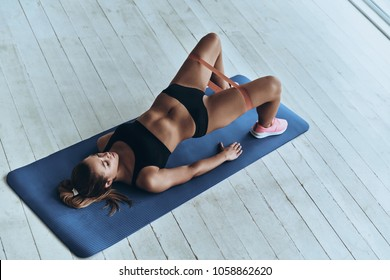 Motivated to shape her body. Top view of young woman in sport clothing bending over backwards using resistance band while exercising in the gym