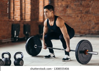 motivated sian guy is preparing to perform deadlift.full length side view photo. lifestyle, hobby, interest