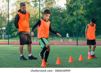 Motivated sporty 13-s boys in orange vests running among the plastic cones during soccer training at the stadium.