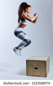 motivated strong woman jumping on the box, strength training, leisure, pastime, full length side view phot, isolated white background, studio shot