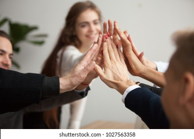 Motivated successful business team giving high five, happy young students employees group join hands with senior teacher mentor, team building unity concept, help support in teamwork, close up view