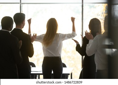 Motivated successful female executive business woman leader get team applause raise hands standing at window celebrating professional victory triumph and corporate success concept, rear back view