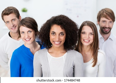 Motivated successful multiethnic business team standing grouped behind a pretty African American woman who is leading the group