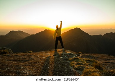 Motivated and Vibrant Man celebrating success on top of a mountain with one arm Raised and Hands Closed