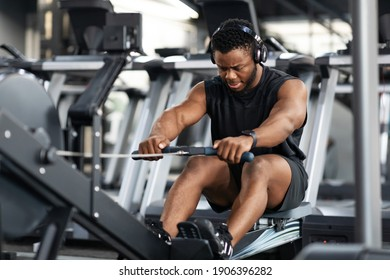 Motivated young black sportsman with wireless headset having workout on rowing machine. Handsome african american man bodybuilder training body on modern block exerciser in gym, copy space